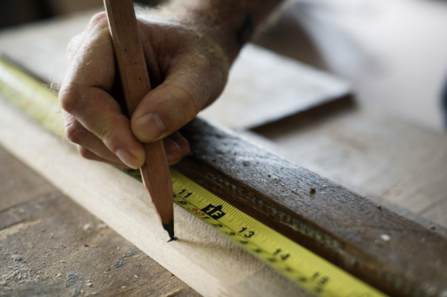 Carpenter using pencil and measurement tape on wood